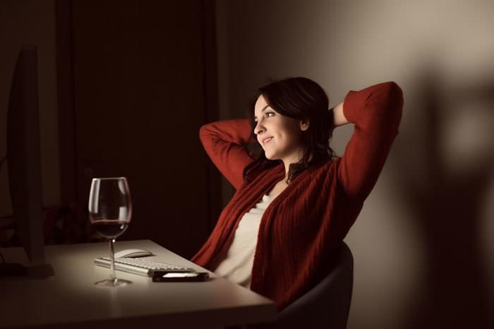 woman flirting online, glass of wine at her side